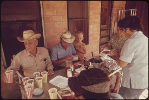 800px-RANCH_FAMILY_IN_THE_LEAKEY,_TEXAS,_AND_SAN_ANTONIO_AREA_EATING_ON_THE_PORCH_OF_THE_BUNKHOUSE_-_NARA_-_554861